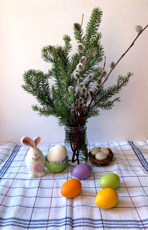 Festive table setting for Easter, colorful eggs, willow twigs, Christmas trees on the table