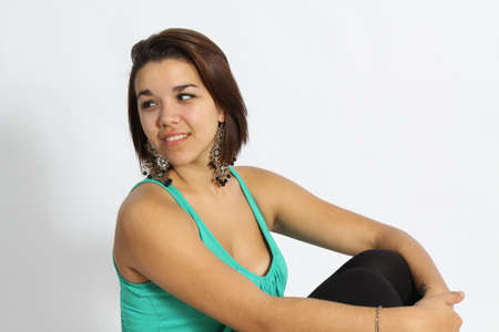 loose fitting: Beautiful Young Brunette wearing a green, loose fitting green top, with black tights on, large earrings, isolated against a light back-drop. Stock Photo