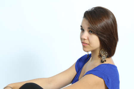 loose fitting: Beautiful young lady wearing a loose fitting, short sleeved, blue shirt, large earrings, bare arms, isolated on a light colored back ground in the studio Stock Photo