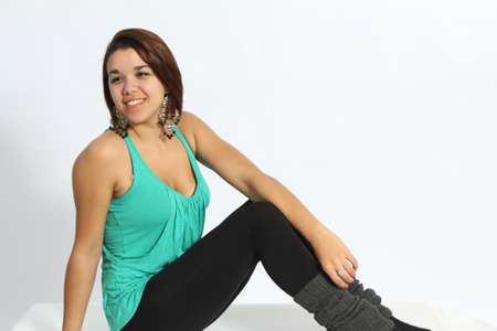 loose fitting:  Beautiful, Young, green-eyed Brunette wearing a green, loose fitting green tank top, with black tights on, large earrings, isolated against a light coloured backdrop. Stock Photo
