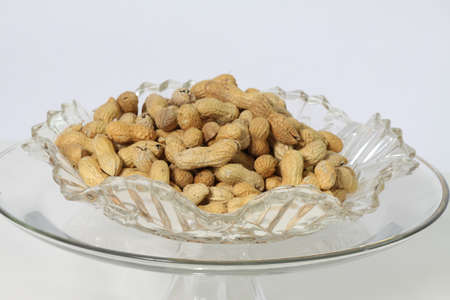 belong: A bowlful of Peanuts in their shell. Peanuts are classified as nuts and belong to the Legume family.