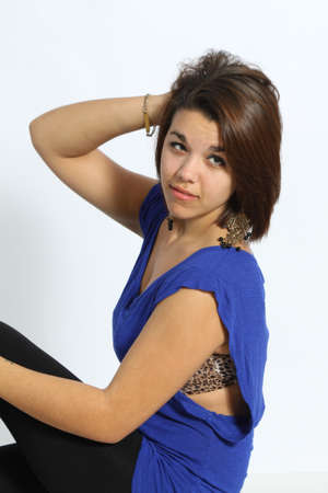 loose fitting: Beautiful, Young, green-eyed Brunette wearing a blue, loose fitting top, with black tights on, large earrings, isolated against a light coloured backdrop. Stock Photo
