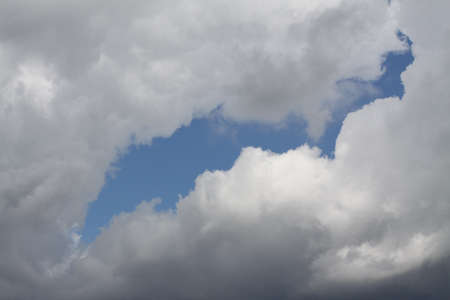 billowing: Billowing white clouds covering the sky with a small piece of blue sky showing