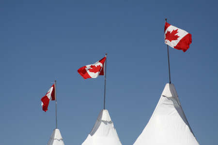 canadian flag: The Canadian Flag,  Maple Leaf  blowing in the wind, framed against an overcast blue sky Stock Photo