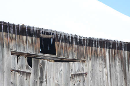 Icicles hanging from overhang on a old wooden barn  版權商用圖片