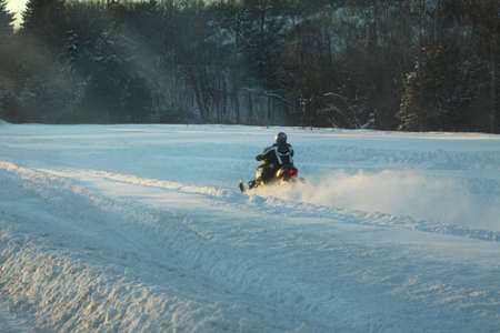 Snowmobile and rider racing past on a snowy trail