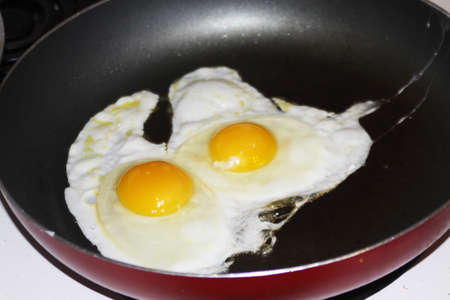 Eggs, Sunnyside up being cooked in a frying pan