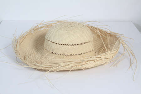 Woven straw hat isolated on a light coloured background
