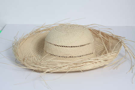 Woven straw hat isolated on a light colored background.