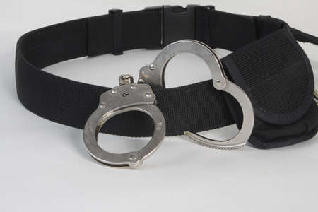 Metal handcuffs draped over a black utility belt against a light colored background  Stock Photo - 18663401