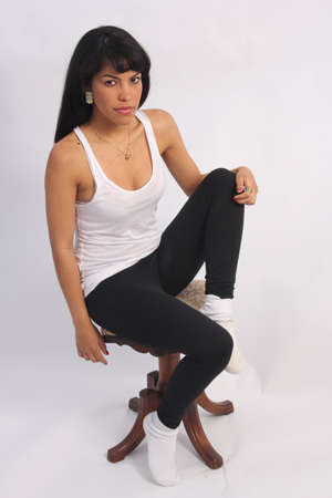 white singlet: Beautiful, young, black-haired Latino in a white singlet with a pretty smile, sitting on small stool