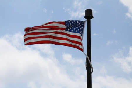 American Flag  Stars   Stripes  gently waving in a light breeze against a blue and cloud filled sky photo