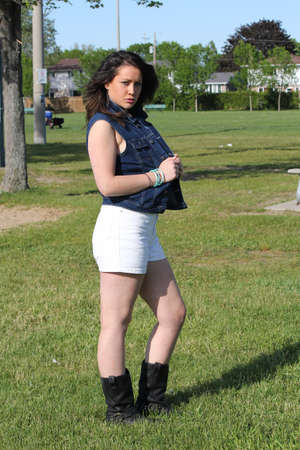 Pretty young brunette in jean vest and white shorts Stok Fotoğraf