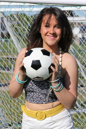 Beautiful young woman with a soccer ball between both hands in front of net Stock Photo