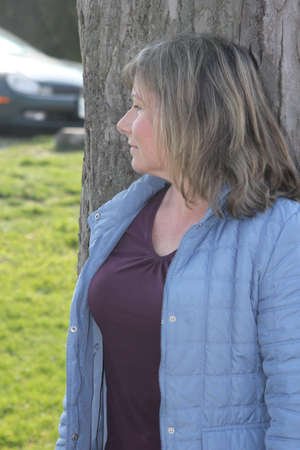 Pretty woman in a blue jacket up against a very large tree