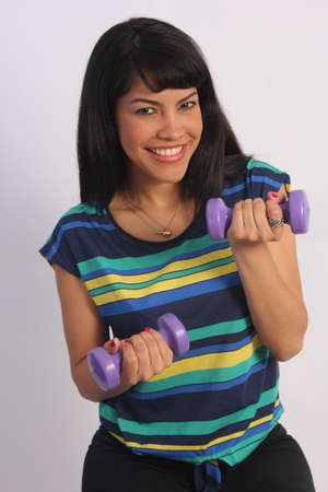 Lovely young woman exercising with a pair of dumbbells