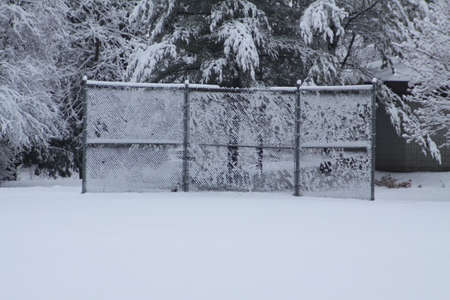 backstop: Fresh wet and sticky snow clinging to a link fence baseball backstop Stock Photo