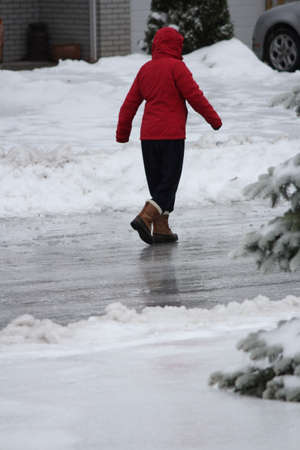 A person walking on a slippery roadway covered with ice