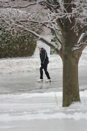 Young girl skating on an ice covered street in a residential area after a freezing rain storm