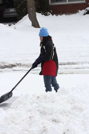 Lady shoveling the deep snow off her driveway after a snow storm  photo