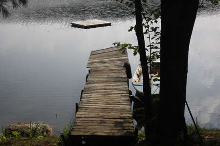 Wooden dock and raft in the water of a small calm lake, Dock is in need of repair