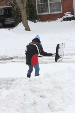 Lady shoveling the deep snow off her driveway after a snow storm.  photo