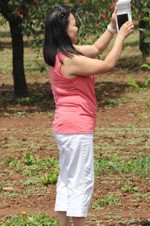 i pad: Lady taking photo with a digital I Pad camera