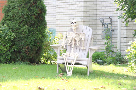 A decorative skeleton of a human, sitting in a yard chair, in preparation for Halloween.