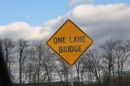 one lane: Yellow warning sign warning of one Lane Bridge ahead