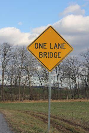 one lane sign: Yellow warning sign warning of one Lane Bridge ahead