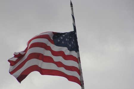 American Flag (Stars & Stripes) waving in a breezy, overcast sky