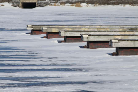 boat dock: Ice covered, wooden boat dock, in a marina, empty of boats during the cold winter months,