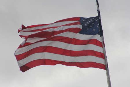 breezy: American Flag (Stars & Stripes) waving in a breezy, overcast sky