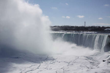 horseshoe falls: Horseshoe Falls at Niagara falls during winter months. mist rising, Ice forming above, below, and beside rushing waters.