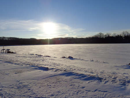 frozen lake: Sun going down and reflecting on a lake of frozen ice.