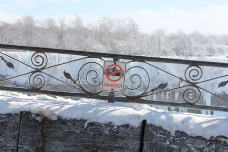 Sign posted on retaining wall warning of danger of climbing railing. Reklamní fotografie - 39846241