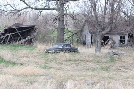 Old abandoned rural property with old car trees and damaged buildings.