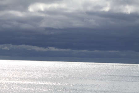 periods: Sky and clouds meet water, overcast afternoon, some sunny periods.
