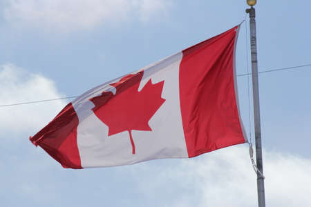 Flag of Canada gently waving in a light breeze against clouds and blue sky. Stock Photo