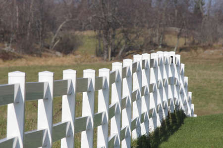 separating: White, wooden fence separating the property at a small farm. Stock Photo