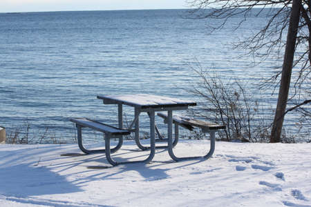 lake front: Snow-covered picnic table on a rise in a lake front park. Stock Photo