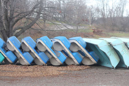 wintering: Rental row and paddle boats stacked on shore on their side, stored and ready for the winter season.