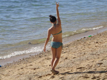 arm extended: Young adult girl in a bikini walking away on a beach with arm extended in the air, fingers forming a peace sign.