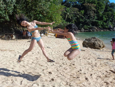 frolicking: Young girls frolicking on the sand at a beach Stock Photo