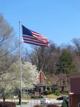 stars and stripes: American Flag (Stars & Stripes) gently waving in a light breeze on top of a pole, at the entrance to a small urban park. Stock Photo