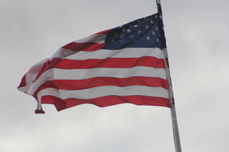 stars and stripes: American Flag (Stars & Stripes) gently waving in a light breeze on top of a pole.