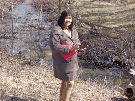 filipina: Mid aged Filipina standing beside a fast moving drainage ditch. Stock Photo