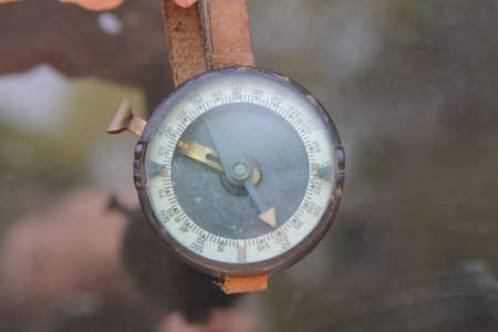 Old Military compass hanging on leather strap