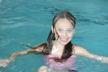 Young girl-child playing around, having fun, in a swimming pool.