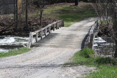 Wooden bridge spanning a fast moving creek full of water
